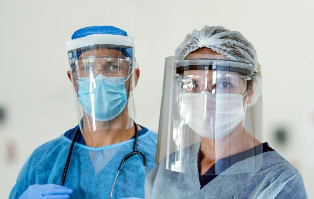 Two healthcare workers with face shields and face masks.