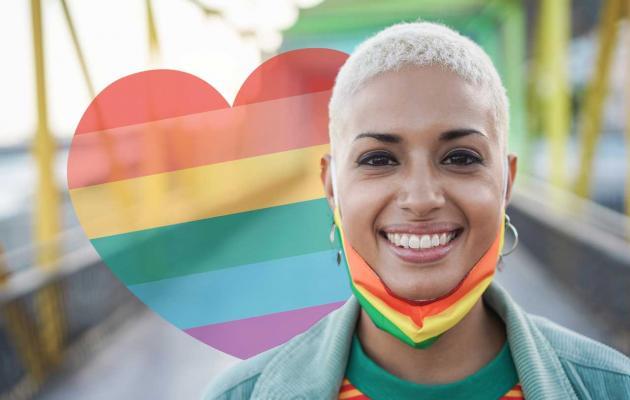Happy woman wearing LGBTQ rainbow flag pride mask