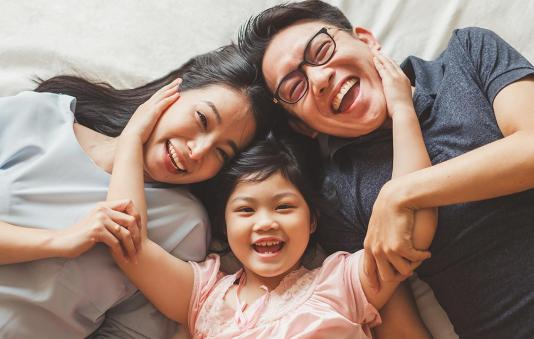 A happy Asian American family laying on a bed.