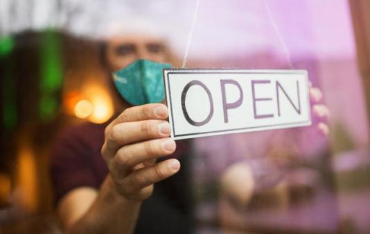 A photo of man holding a sign that says open.