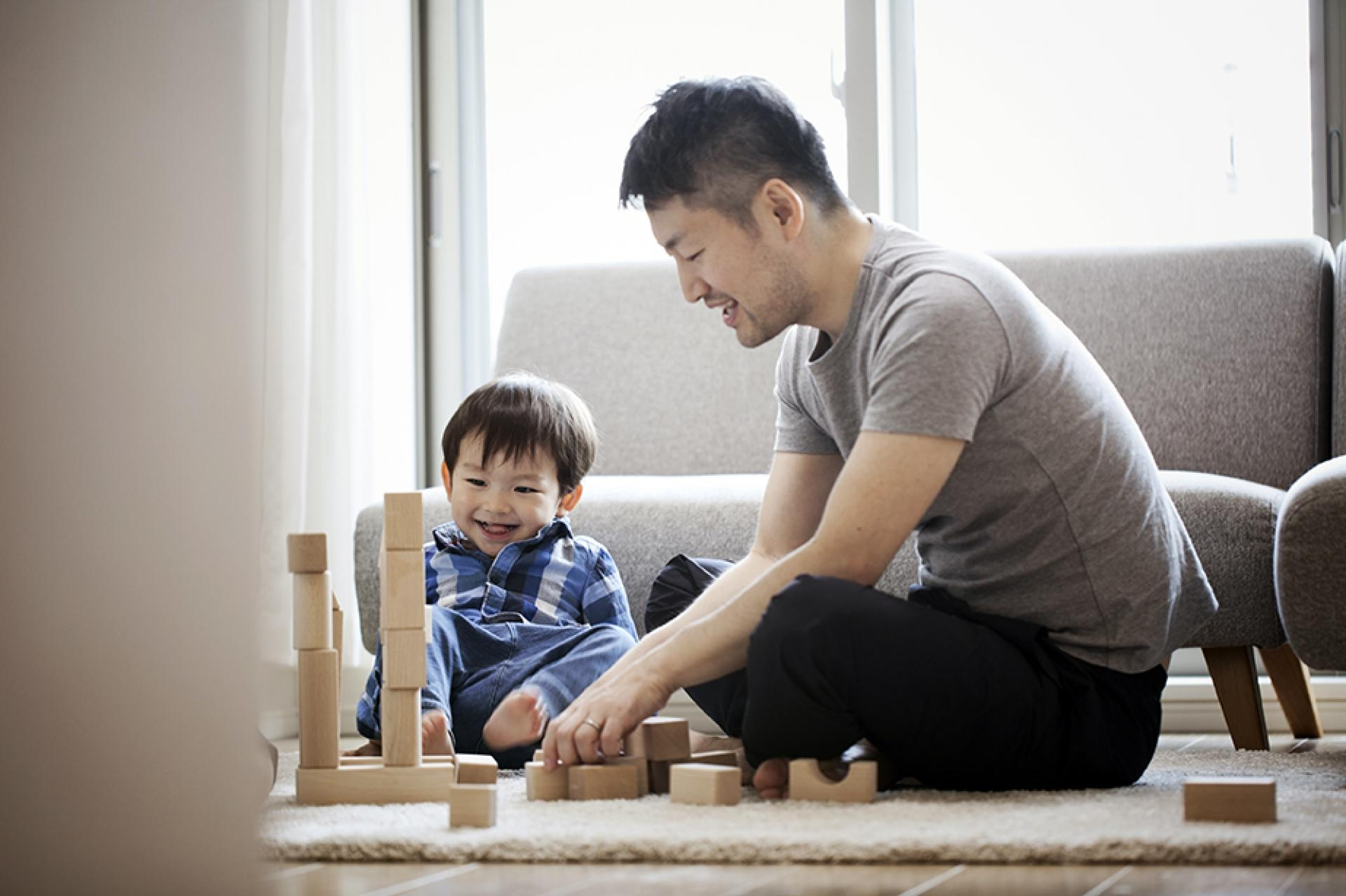 Man sitting with child playing with blocks