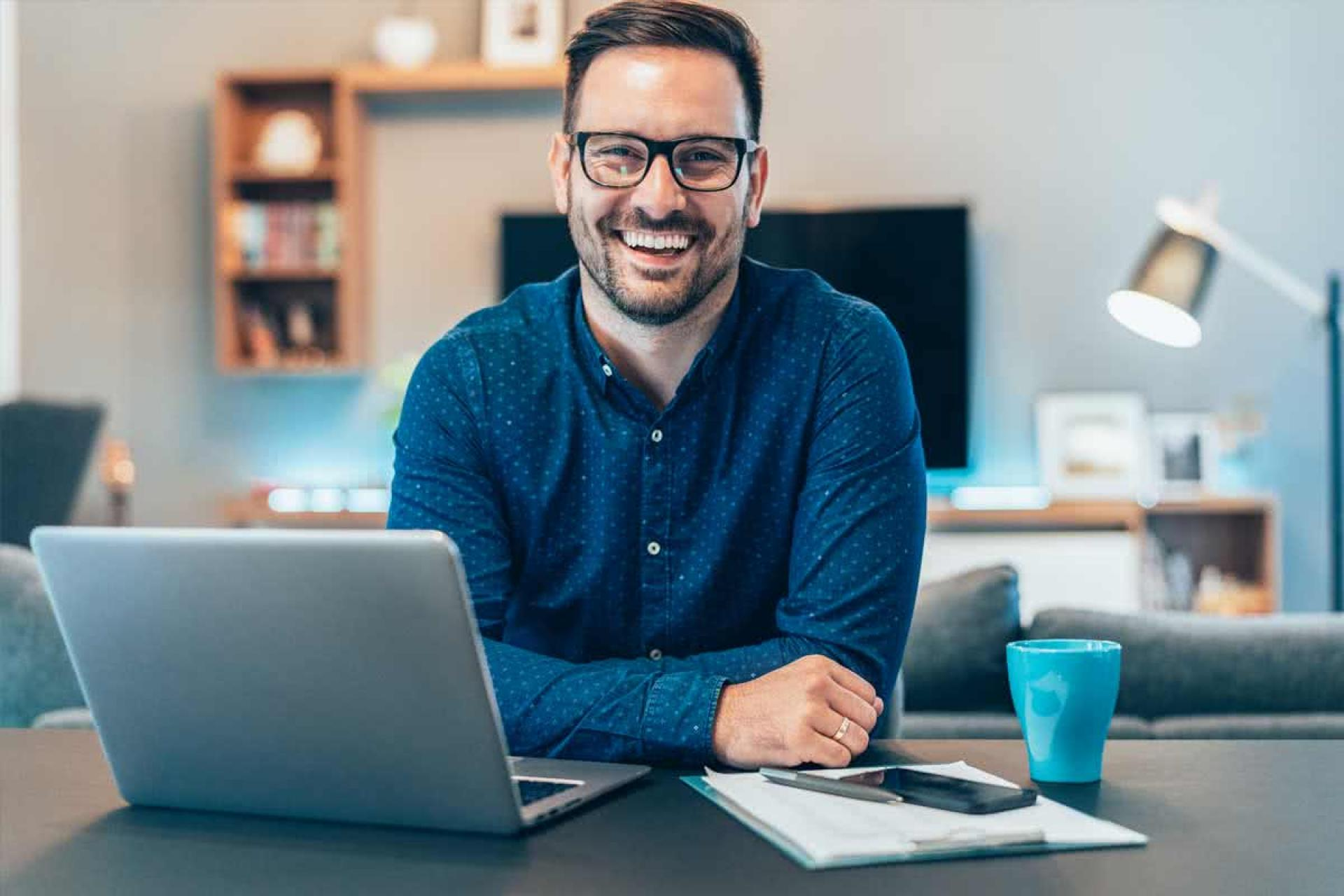 Man with glasses and a laptop smiling