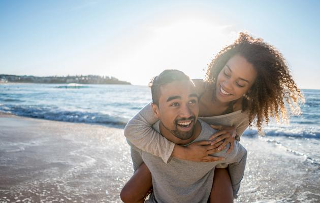 Couple on beach piggy back