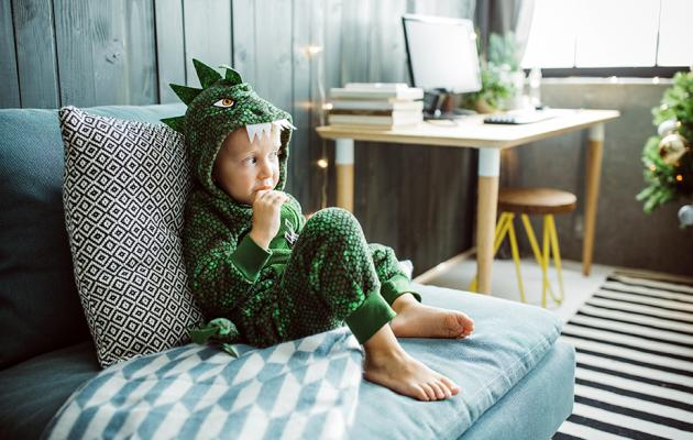 Child wearing a dinosaur costume watching TV