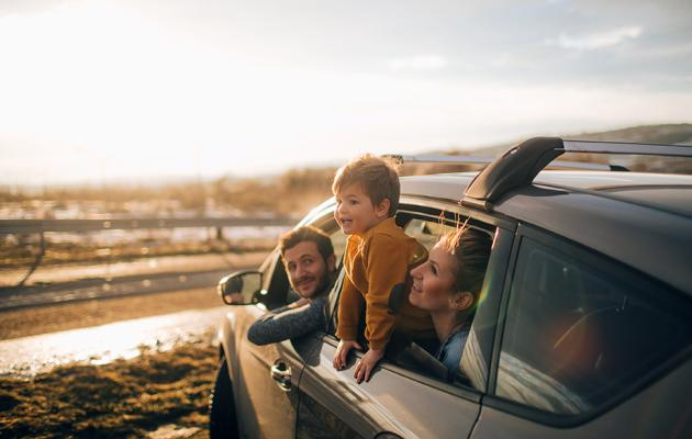 Family in car on beach, child hanging out of window