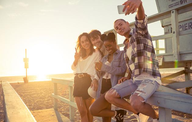 Young people on beach doing group selfie