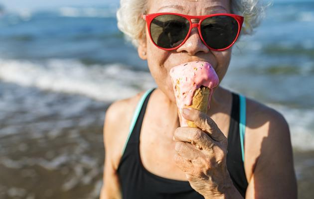 Grandma eating ice cream on beach