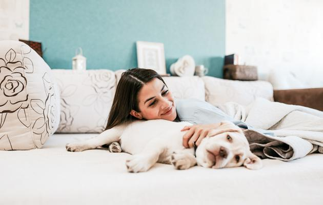 Young woman on bed petting and leaning on dog