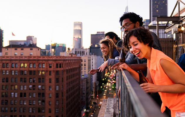 Party group overlooking city from rooftop