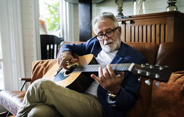 Senior man playing guitar in living room
