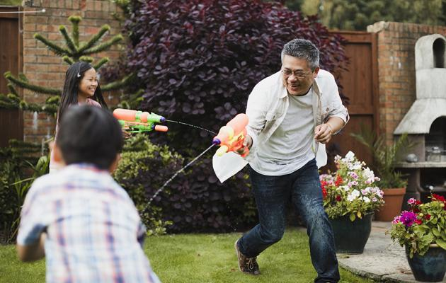 Asian family playing water guns on front lawn