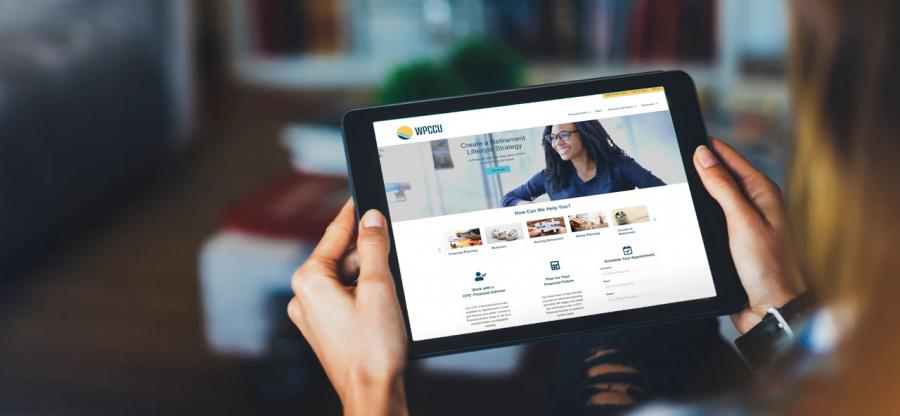 A woman is holding a tablet. The display of the tablet displays a new website.