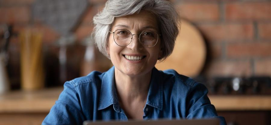 A smiling mature woman with glasses is using her laptop.