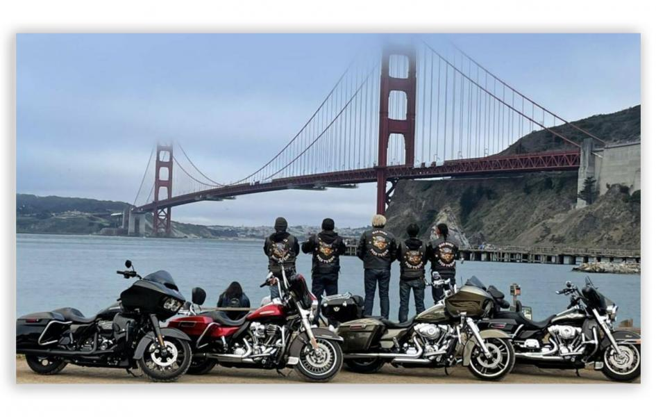 A photo of a group of motorcycle riders standing in front of a bridge.