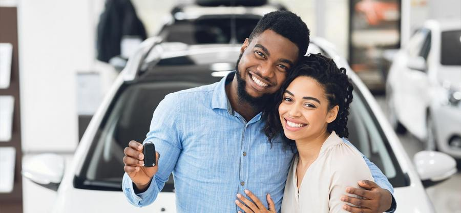 A happy African couple is standing in front of their new car.