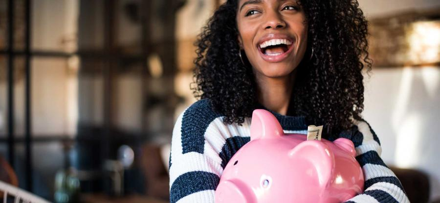 A joyful African-American woman is holding a oink piggy bank in her arms.